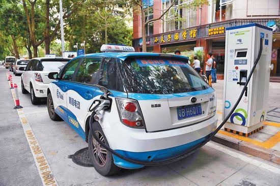 图为出租车正在使用宜停车泊位上设立的充电桩充电。