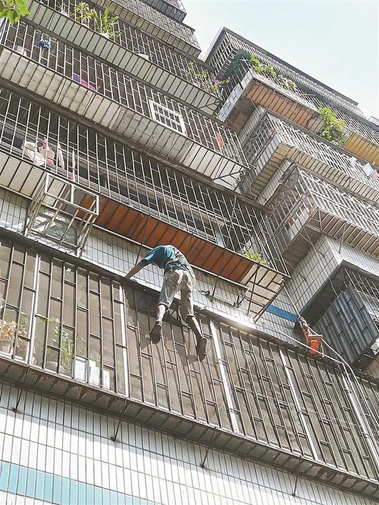 一名散工正攀爬在阳台外帮租户安装遮挡铁皮。