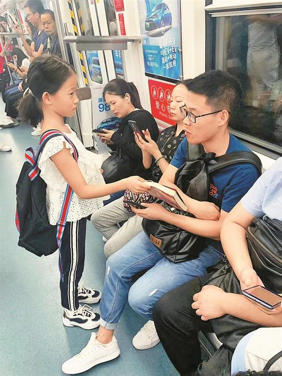 ▲续蔓其给地铁上的乘客送书。