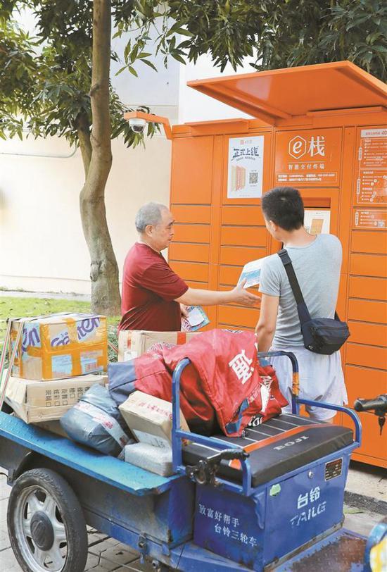 ▲快递工作人员正在帮市民收取快递。