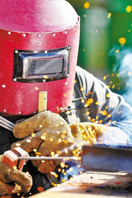 在太阳下进行电焊作业的建设者。