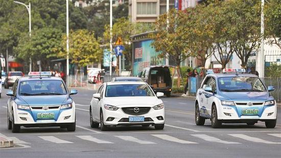 """▲""""深圳出租""""上线试运营。出租车司机可通过高德地图在线接单。图为路上行驶的电动出租车。 深圳晚报记者 张焱焱 摄"""