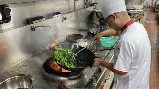 丁仁军挥铲炒菜。