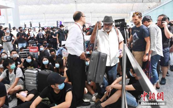 资料图:8月13日下午,大批示威者堵塞香港国际机场1号客运大楼旅客登机行段及保安闸门。中新社记者 麦尚旻 摄