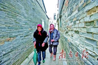 两位老人相互搀扶着走过幽深的楼村麻石巷。赖远美 摄