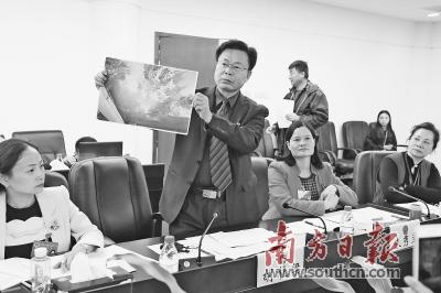 人大代表胡桂梁现场展示饮水源保护区污染照片。南方日报记者 朱洪波 鲁力 摄