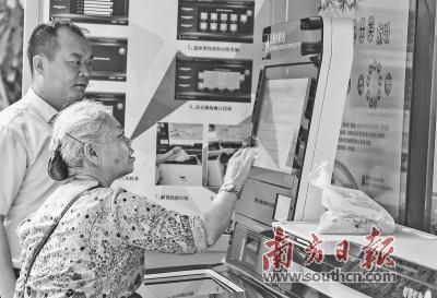 在深圳市盐田区上东湾小区,一名老人在物业管理人员的指导下给厨余垃圾称重。居民通过垃圾分类称重可以获得积分,并获得不同的小奖励。 新华社发