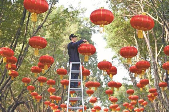工作人员正在挂红灯笼。 冯明 摄