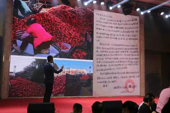 主持人在新春嘉年华上播报四川攀枝花米易县蔬农番茄积压滞销的情况。