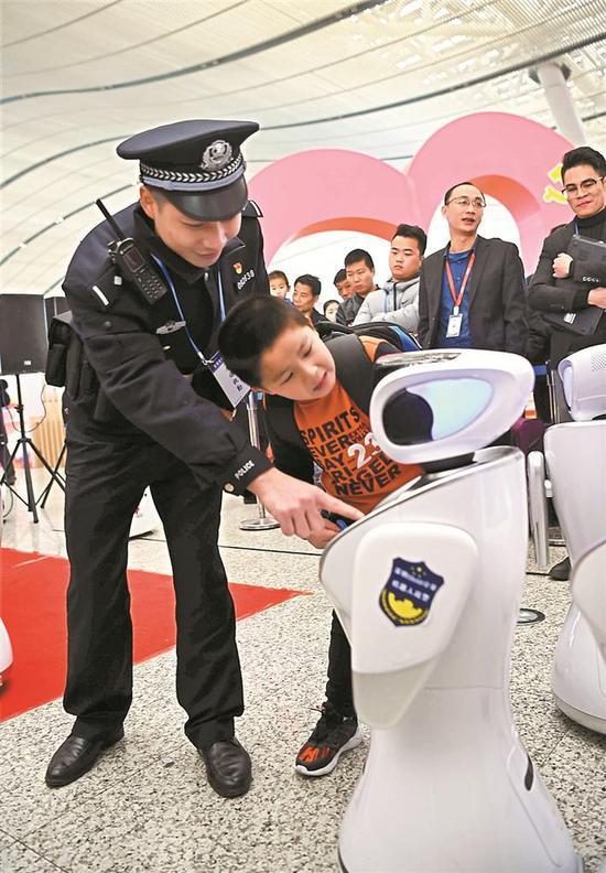▲警务人员指导小朋友操作机器人。 本版图片均由深圳晚报记者 冯明 摄