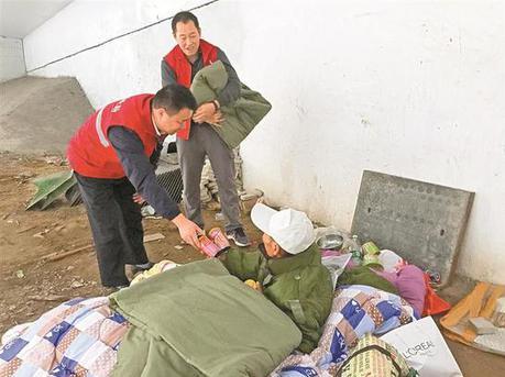 寒风中为街头流浪者送去衣物食物