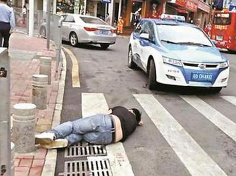 醉汉清晨睡在马路上 好心的哥守护半小时
