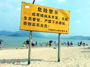 较场尾海滩上,戏水者对警示牌视若无睹。