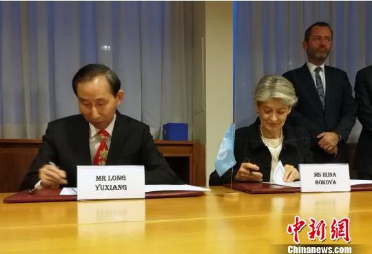 图为中国全国政协外事委员会委员、中国国际文化传播中心执行主席龙宇翔和联合国教科文组织总干事伊琳娜·博科娃签署协议。 刘思敏 摄