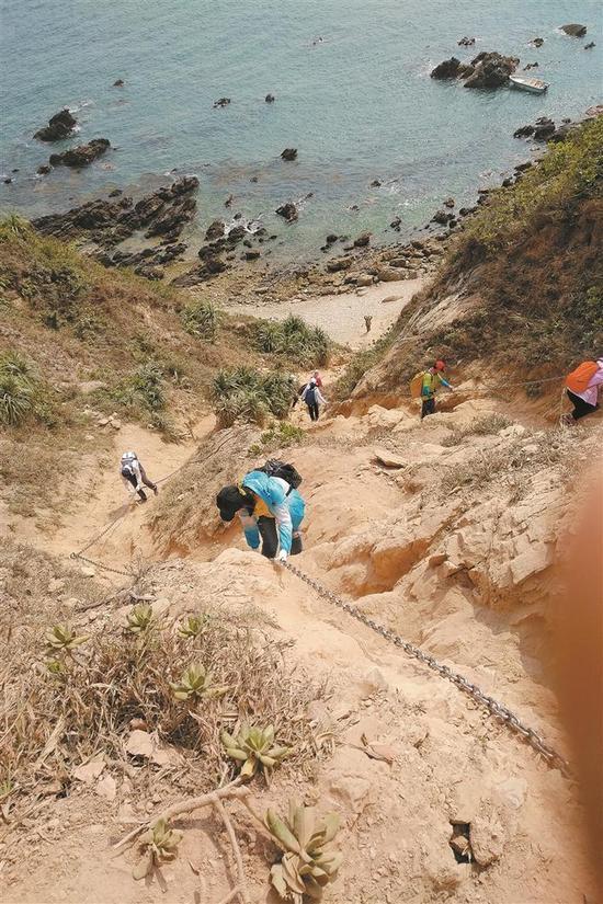 ◀在陡峭处,游客只能缓缓攀爬。 本版图片除署名外 均由深圳晚报记者 李剑南 摄