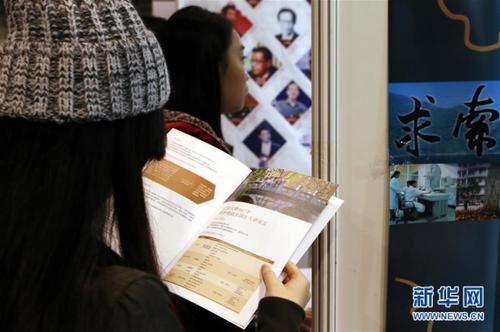 资料图:2016年12月17日,香港学生在查看2016内地高等教育展北京大学展位上的资料。新华社记者 李鹏 摄