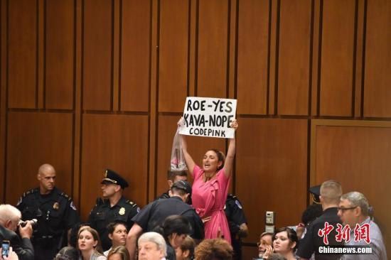 抗议卡瓦诺出任大法官的民众被警方带出听证会大厅。 中新社记者 邓敏 摄
