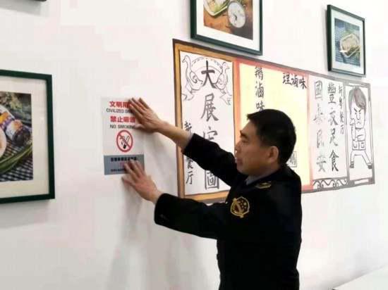 莲湖区食药监局工作人员在饭店张贴禁烟标识