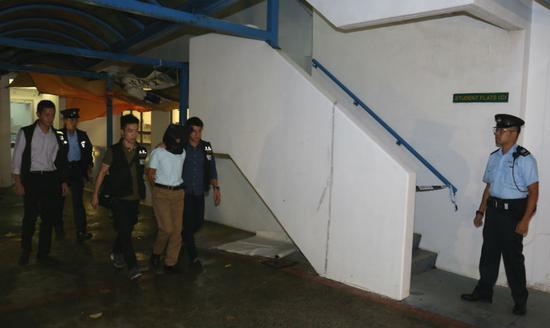 张祺忠身着白色上身、卡其色西裤,被警方用黑布蒙头押往住所搜查/图自港媒