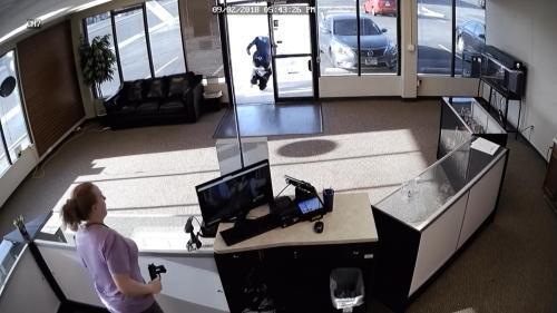 劫匪落荒而逃,女店员捡起枪。(图片来源:奥罗拉警察局社交账号视频截图)