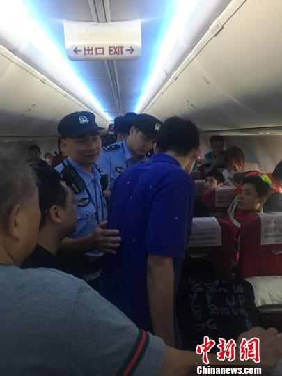 机场警察将打开应急门的男乘客(蓝衣者)带离。 钟欣 摄