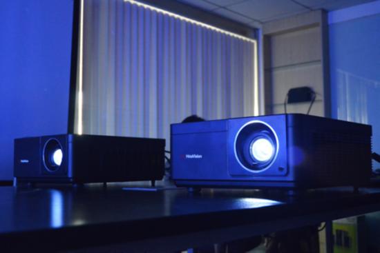 两台HT-G62U并排摆放在桌面上,投影1×2超宽幅画面。