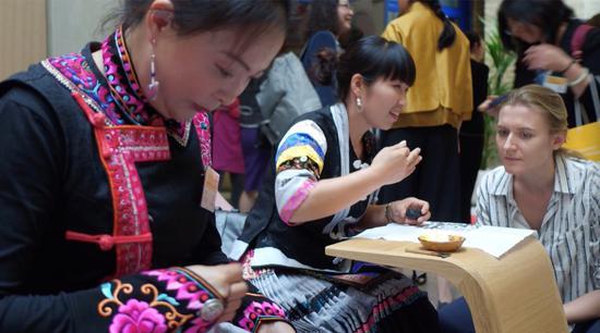 来自彝族和苗族的绣娘向中外来宾展示精湛的传统非遗手工技艺