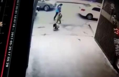 女孩路口玩耍遭轿车前后轮碾压 站起后淡定离开