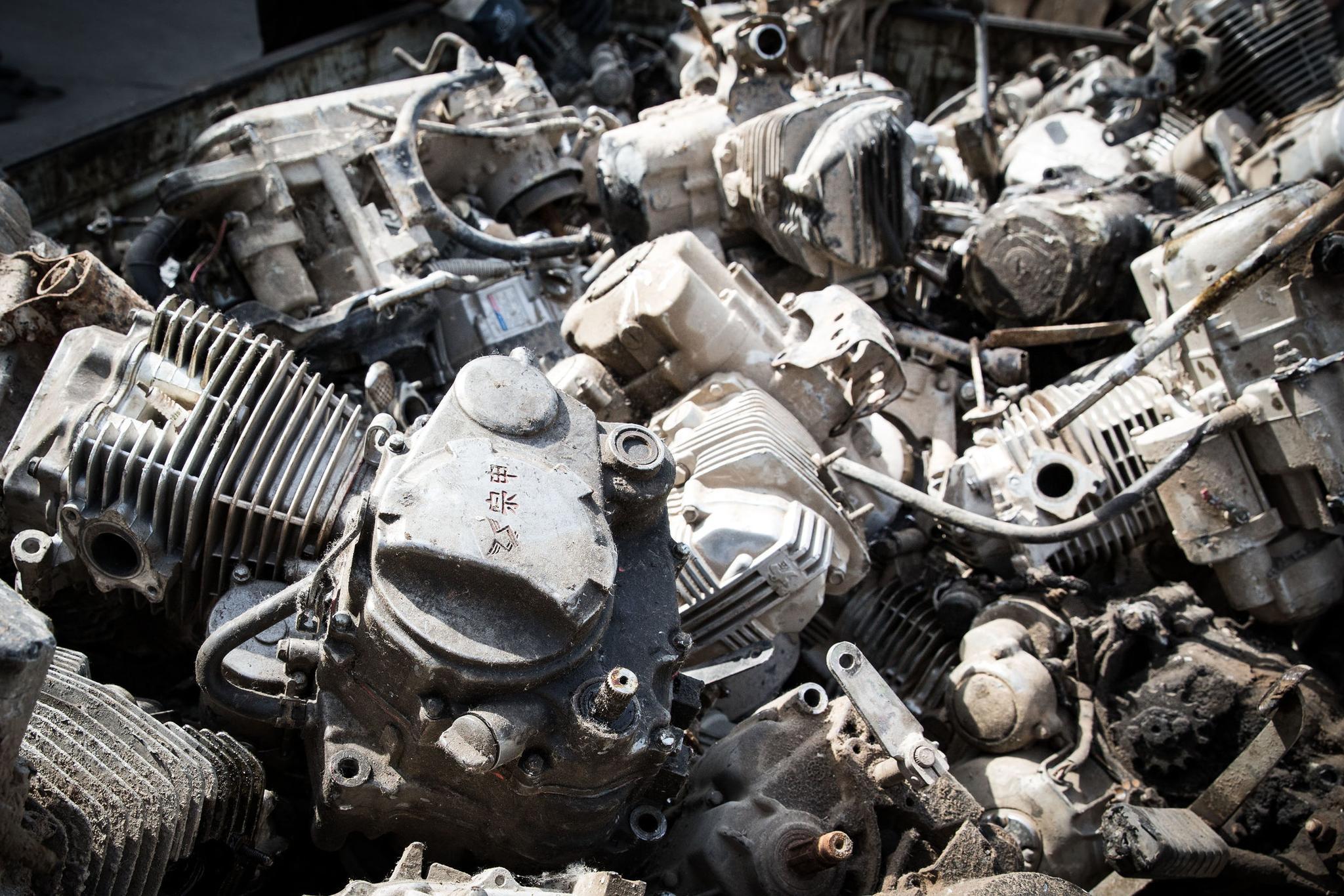废旧摩托车被送到回收站做拆解处理,发动机堆