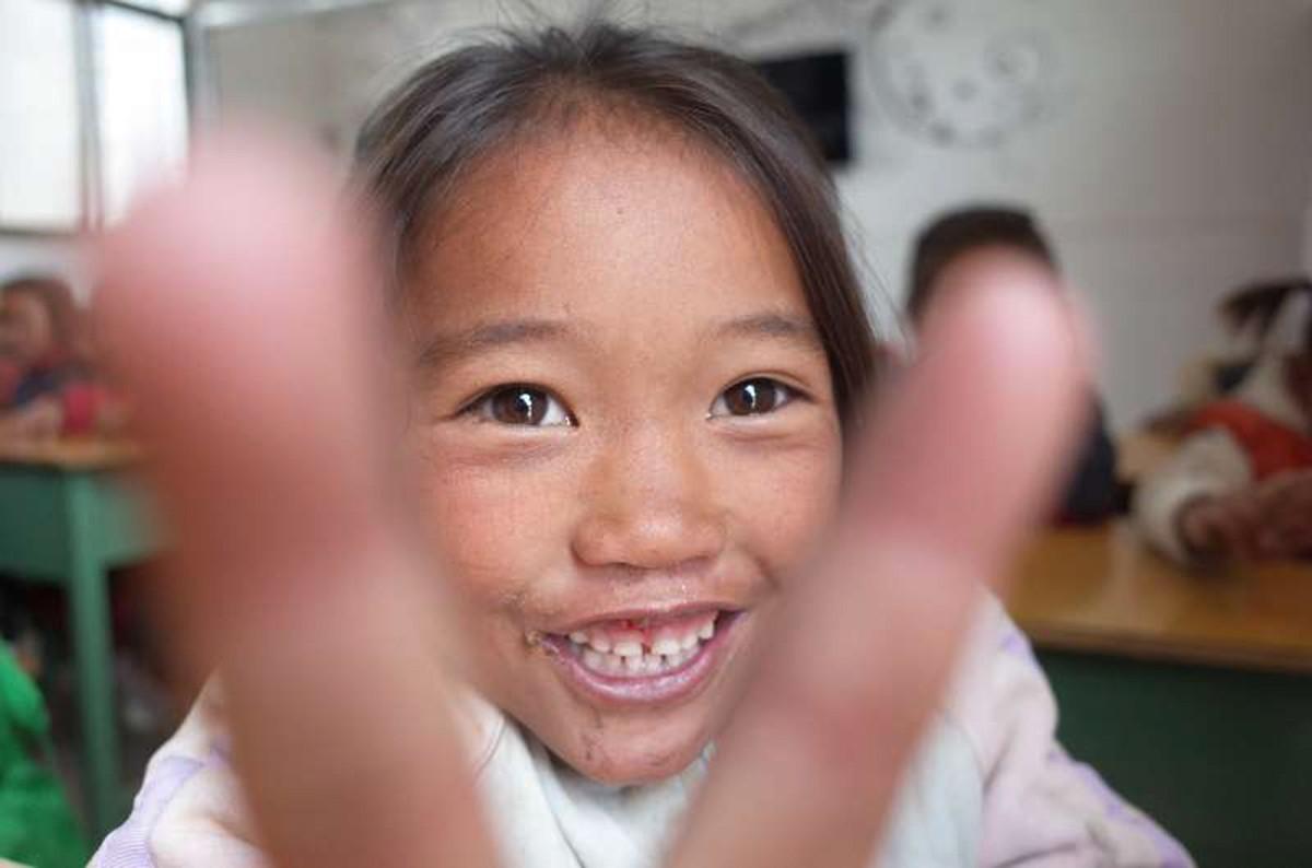 一位阳光可爱的小女孩儿笑的很开心,她比出一个剪刀手,让摄影师给她拍