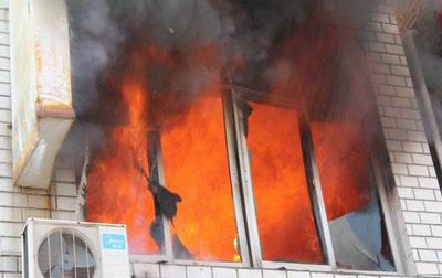 女子被困火中 红衣大叔爬窗单手救人