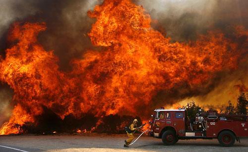 鉴于火势失控,加州森林及防火局的一名消防员急忙转移到安全处.图片