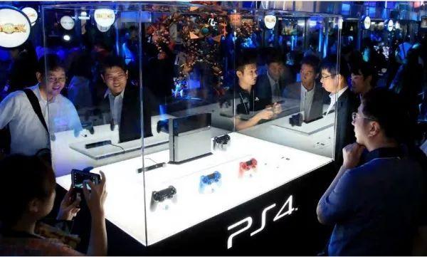 访客和媒体记者在2013年的东京电玩展上参观PS4游戏机