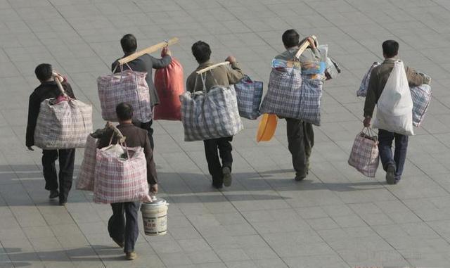 南京火车站广场上,农民工挑着行李准备乘坐火车返乡.