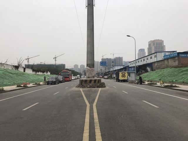路口的电杆约100米处也立有一根电杆,四周也建有限速和限高栏及安全岛