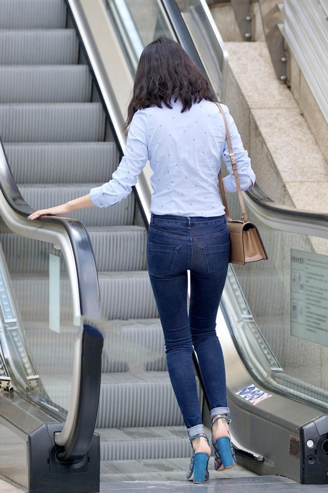 街拍:蓝色紧身牛仔裤+白色长袖衬衫的美女,修