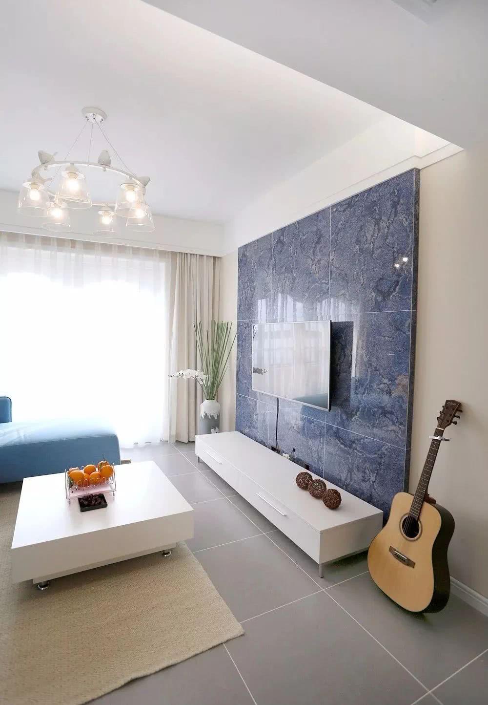 客厅电视墙以丹蓝色瓷砖做造型,壁挂电视机下方白一个白色电视柜