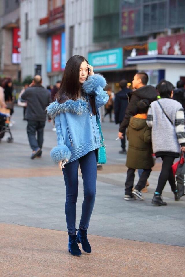 时尚街拍美女:紧身牛仔裤搭配蓝色针织衫的美女,小姐姐的五官挺精致啊