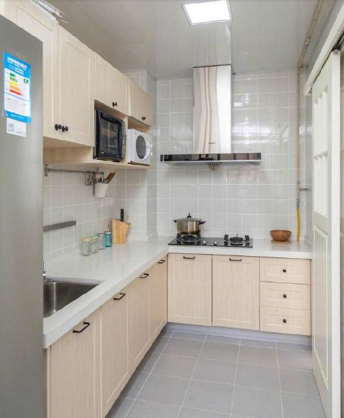 厨房,正方形的地砖和墙砖,吊柜上放着微波炉等电器,很好用.