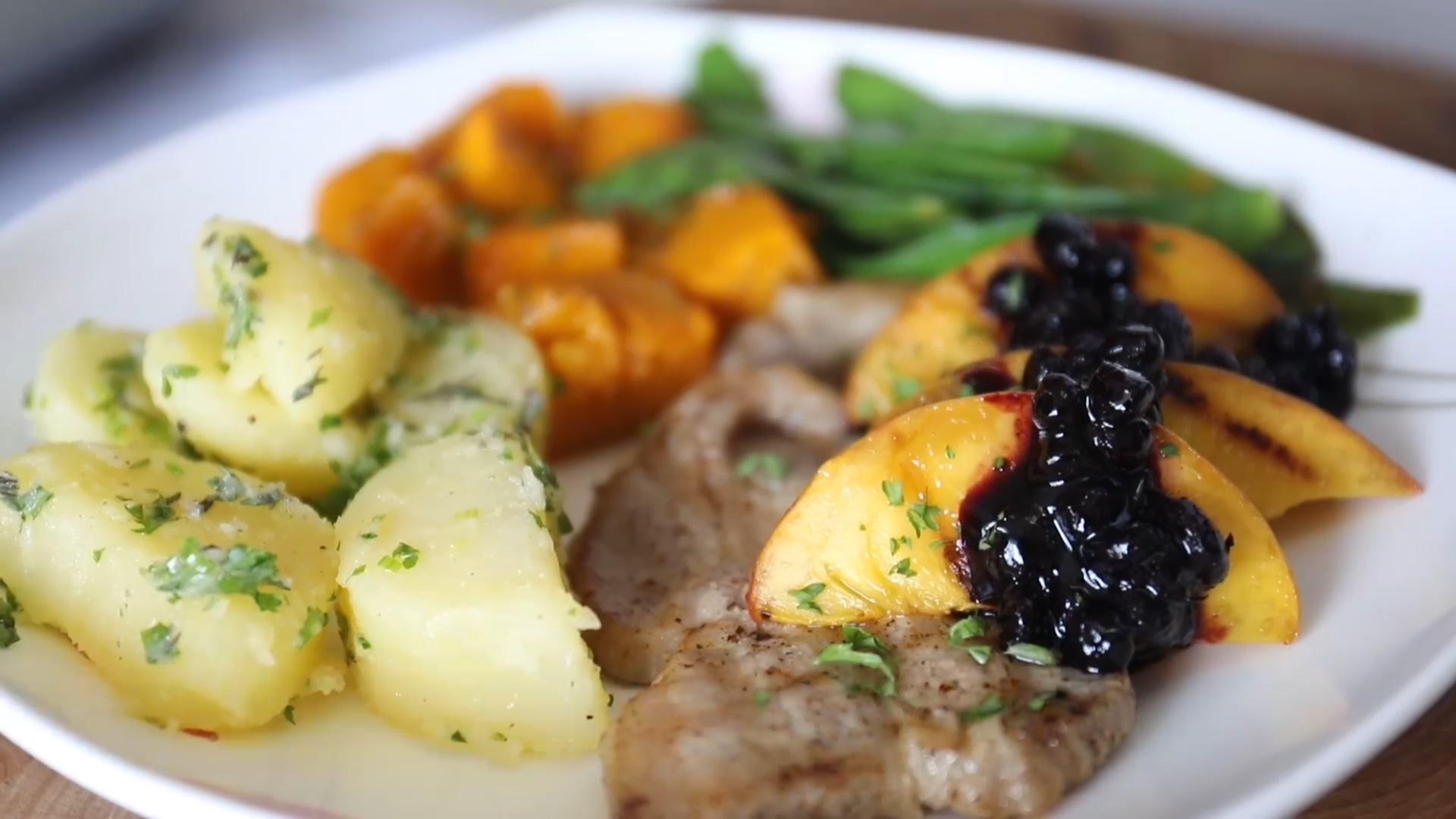 厨师腌制加拿大猪肉排后烤熟,配蓝莓果酱酱汁做西餐!