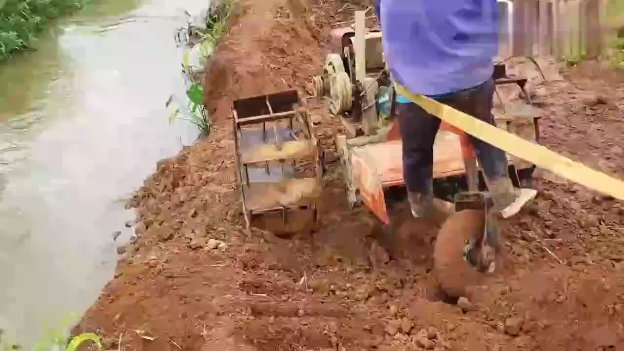 还是第一次见这样的手扶拖拉机不过很实用过河一点也不含糊