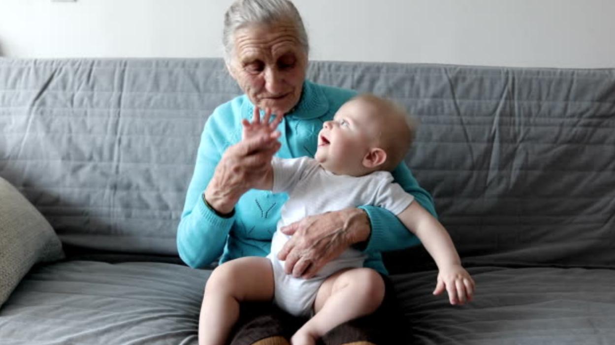 奶奶抱着已睡的宝宝去婴儿床,不料一起载进床里,宝宝醒来一脸懵