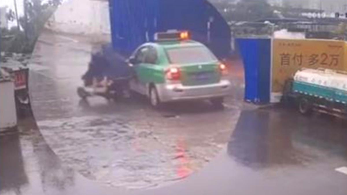电瓶车擦挂出租人车倒地 1件雨衣竟装下4个人