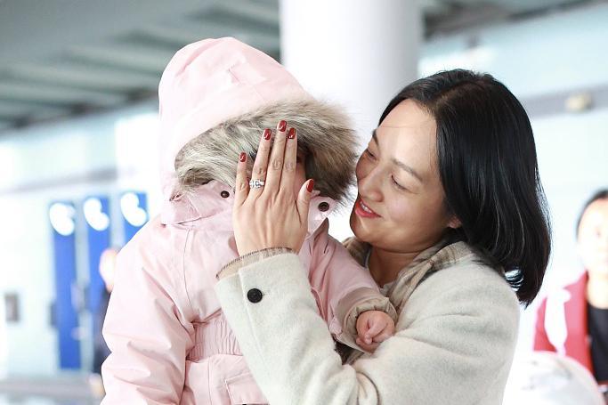 朱丹素颜现身机场抱娃大方任拍,为女儿挡风遮脸婚戒抢镜