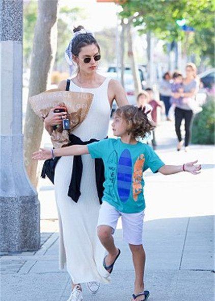 安布罗休带娃现身街头,穿开叉白裙秀长腿,牵手儿子疾走气场强