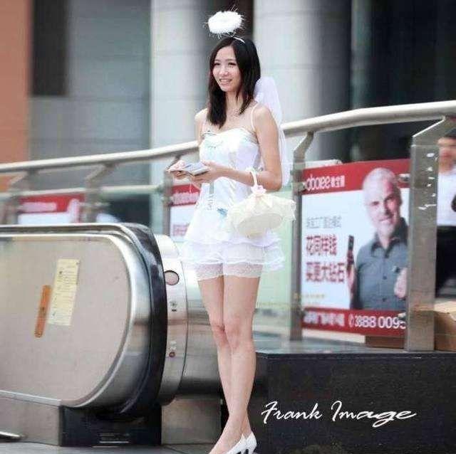 街拍: 穿着白色裙子发传单的学生妹, 纯洁像天使, 让人无法拒绝