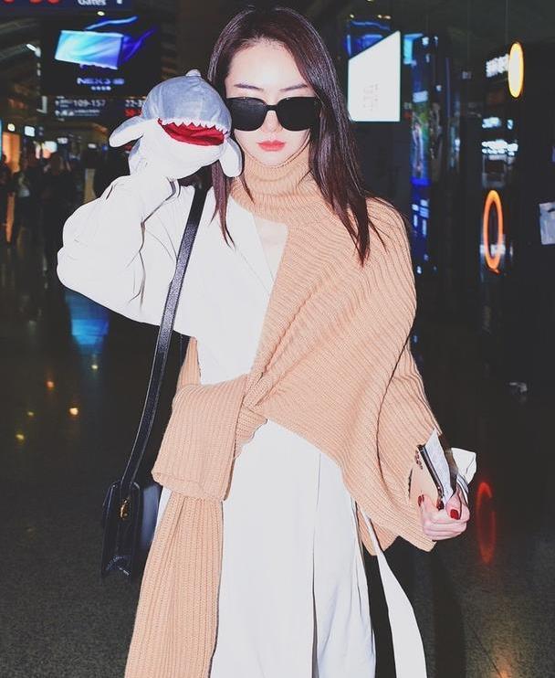 戚薇叠穿风走机场,白色大衣叠穿奶茶色毛衣,手拿玩偶太少女