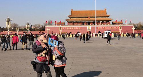 天安门广场上,寒风中给游客拍照的摄影师生意冷淡,却依然在坚持