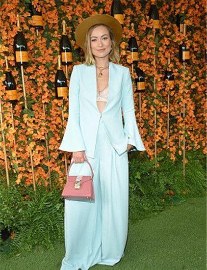 奥利维亚·维尔德:天蓝色喇叭袖裤装,花朵粉包清新干练