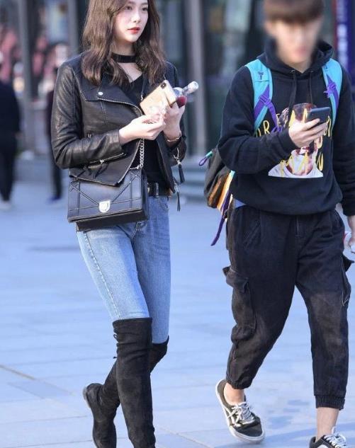 身穿牛仔长裤的过膝靴美女,长发飘飘,身材性感苗条